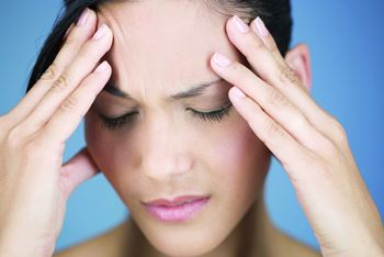 Frau mit Kopfschmerzen undd Migräne