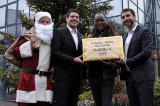 """Ein Weihnachtsgeschenk für """"Schulbausteine für Gando"""": Hevert spendet 15.000 Euro für das Schulbauprojekt in Burkina Faso. Bei der Scheckübergabe v.r. Mathias Hevert, Francis Kéré und Marcus Hevert."""